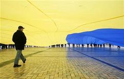 <p>Мужчина проходит под огромным национальным флагом во время празднования Дня соборности Украины в Киеве 22 января 2009 года. Украина и США обсуждают возможность использования американцами украинских радиолокационных станций раннего обнаружения ракетных пусков (РЛС), от которых в начале этого году отказалась Россия, сказал посол Украины в США Олег Шамшур. REUTERS/Gleb Garanich</p>