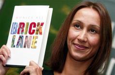 <p>Novelist Monica Ali holds up her book 'Brick Lane' in London, October 14, 2003. REUTERS/Stephen Hird</p>