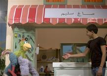 <p>Palestinian actor Ezzat Natsheh speaks with puppet Kareem, operated by puppeteers Shaden Zamamiri and Raja'e Sandoqa, during the filming of a scene on the set of Shara'a Simsim in a studio in the West Bank city of Ramallah October 20, 2009. REUTERS/Fadi Arouri</p>