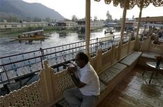<p>The owner of a houseboat rests on the deck of his houseboat on the waters of Dal Lake in Srinagar October 22, 2009. For nearly a century, hand-carved houseboats bobbing on a placid lake drew millions of visitors to the stunningly beautiful Himalayan region of Kashmir. But the number of ornate boats is dwindling because of an 18-year-old ban on new construction of cedarwood houseboats and strict rules on renovation. Picture taken October 22, 2009. REUTERS/Fayaz Kabli</p>