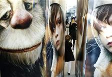 """<p>Una mujer toma una fotografía de su hija entre afiches del filme """"Where The Wild Things Are"""" en Nueva York, 13 oct 2009. El filme de terror de bajo presupuesto """"Paranormal activity"""" se impuso en la taquilla cinematográfica de Estados Unidos, derrotando a la sexta entrega de la saga """"Saw"""" con una recaudación de 22 millones de dólares en el fin de semana anterior a Halloween. El campeón de la semana pasada, """"Where the Wild Things Are"""", una adaptación del aclamado libro infantil de Maurice Sendak dirigida por Spike Jonze, cayó al tercer lugar con 14,4 millones de dólares. REUTERS/Lucas Jackson/Archivo</p>"""
