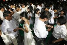 <p>Brides and grooms exchange rings during a mass wedding in Muntinlupa city, south of Manila February 14, 2008. REUTERS/Romeo Ranoco</p>