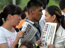 """<p>Жительницы Киргизии держат в руках газеты на улице города Ош 8 июля 2005 года. В городе Ош на юге Киргизии трое неизвестных избили замредактора государственной областной газеты, сообщила Рейтер сотрудник местного фонда """"Журналисты"""" Мери Бекешова, связывая этот инцидент с его профессиональной деятельностью. REUTERS/Gleb Garanich</p>"""