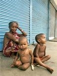 """<p>Семья нищих сидит напротив закрытого магазина, индийский штат Ассам 18 августа 2004 года. Няня из индийского города Бангалор была уволена из-за того, что она регулярно накачивала ребенка, с которым сидела, снотворным и затем сдавала его """"в аренду"""" уличным беднякам за $2 в час, сообщили газеты в пятницу. REUTERS/Utpal Baruah</p>"""