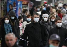 """<p>Люди в защитных масках в центре Назрани 4 ноября 2009 года. Вспышка """"свиного"""" гриппа, уже унесшая в России 19 жизней, вызвала ажиотажный спрос на противовирусные лекарства и защитные маски среди населения. REUTERS/Kazbek Basaev</p>"""