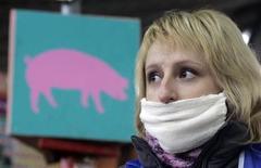 """<p>Мясник в защитной маске на рынке в Киеве 10 ноября 2009 года. Люди, несколько раз болевшие обычным гриппом (или же несколько раз проходившие вакцинацию), возможно, в некоторой степени защищены от вируса """"свиного"""" гриппа, сообщили американские исследователи в понедельник. REUTERS/Konstantin Chernichkin</p>"""