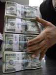 <p>Сотрудник Korea Exchange Bank держит в руках пачки долларовых купюр в Сеуле 3 ноября 2009 года. Грабители на юге Тайваня получили в понедельник небывалый куш. Им удалось ограбить свою жертву, забрав у неё более чем $2 миллиона наличными. REUTERS/Jo Yong-Hak</p>
