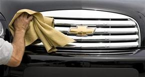 <p>A worker cleans the front grill of a Chevy HHR at a General Motors dealership in Montreal, June 1, 2009. Reuters/Christinne Muschi</p>