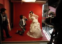 <p>An engaged Chinese couple strike a pose for their wedding photographs at a studio in central Beijing November 27, 2009. REUTERS/David Gray</p>