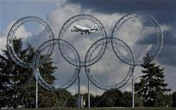 <p>A jet coming into land is framed in the Olympic Rings along the road leading to the international airport in Vancouver, British Columbia March 5, 2009. REUTERS/Andy Clark</p>