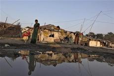 <p>Una donna col figlio in uno slum vicino all'impianto di pesticidi Union Carbide a Bhopal. REUTERS/Reinhard Krause</p>