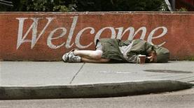 <p>A homeless woman lies on a sidewalk using an empty coffee cup to collect spare change from passers-by in downtown Vancouver, British Columbia June 29, 2007. REUTERS/Andy Clark</p>