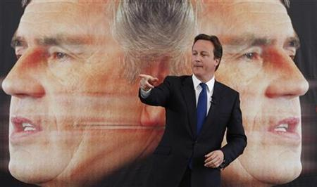 Leader of the Conservative Party, David Cameron, speaks in front of a campaign poster showing Prime Minister Gordon Brown, London April 27, 2009. REUTERS/Andrew Winning