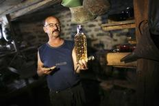 <p>Sando Trenchev, 60, shows a bottle of homemade plum rakia brandy in a cellar in his house in the village of Oreshak, western Bulgaria November 23, 2009. REUTERS/Stoyan Nenov</p>