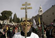 <p>A member of the clergy takes part in the annual Christmas procession outside the Church of the Nativity in the West Bank town of Bethlehem December 24, 2009. REUTERS/Ammar Awad</p>