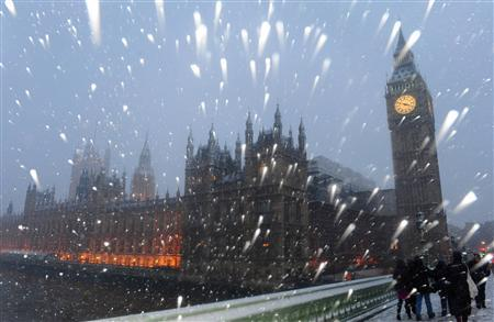 Snow falls around The Houses of Parliament in central London, January 6, 2010. REUTERS/Toby Melville