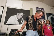 <p>Elvis fan Ulf Bender of Germany poses with a microphone that Elvis used at Sun Studios in Memphis, Tennessee where Elvis recorded several of his first songs on August 16, 2007. REUTERS/Lucas Jackson</p>