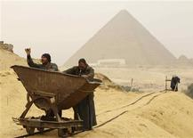 <p>Trabalhadores atravessam local onde uma nova coleção de tumbas foi encontrada ao lado da pirâmide de Khufu, no dia 11 de janeiro. Novas tumbas encontradas em El Giza apóiam a visão de que as Grandes Pirâmides foram construídas por trabalhadores livres e não por escravos, como se acreditava. REUTERS/Tarek Mostafa</p>