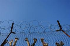 <p>Иммигранты у ограды в центре временного содержания в Пагани, Греция 19 октября 2009 года. Ситуация с гражданскими свободами в мире продолжила ухудшаться в 2009 году, свидетельствуют результаты ежегодного исследования американской правозащитной организации Freedom House. REUTERS/John Kolesidis</p>