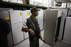 <p>Солдат Национальной гвардии Венесуэлы во время инспекции одного из магазинов в Ла-Гуайре 12 января 2010 года. Венесуэльские чиновники при поддержке солдат временно закрыли десятки розничных точек, продавцы которых были обвинены в необоснованном повышении цен. REUTERS/Jorge Silva</p>