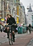 <p>A women talks on her mobile phone while riding a bike in Amsterdam, January 17, 2007. REUTERS/Koen van Weel</p>