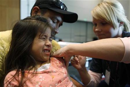 Ashley Estrada, 6, reacts as she gets a shot of the H1N1 flu vaccine at a H1N1 clinic held in Arlington, Texas November 24, 2009. REUTERS/Jessica Rinaldi