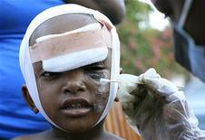 <p>Un bimbo ferito nel terremoto ad Haiti viene curato da un medico in un presidio sanitario organizzato per la strada a Port au Prince. REUTERS/Kena Betancur</p>