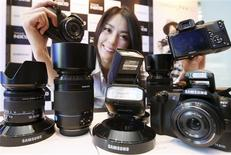<p>Le NX10 de Samsung Electronics, un nouvel appareil photo numérique de la forme d'un compact mais équipé d'une optique interchangeable comme les modèles reflex. Grâce notamment à ce modèle hybride, le géant sud-coréen de l'électronique veut porter sa part de marché dans les appareils photo numériques compacts à 15% d'ici la fin de l'année. /Photo prise le 19 janvier 2010/REUTERS/Kim Hyun-Tae/Yonhap</p>