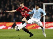 <p>Carlos Tevez (dir.) do Manchester City desafia Michael Carrick do Manchester United durante jogo do Copa da Liga Inglesa no estádio de Manchester ao norte da Inglaterra. Tevez marcou dois gols, dando à sua equipe uma vitória de 2 x 1. REUTERS/Phil Noble 19/01/2010</p>