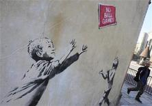 <p>A pedestrian passes graffiti art on a wall in north London, September 24, 2009. British media have attributed the new work to acclaimed British street artist Banksy. REUTERS/Toby Melville</p>