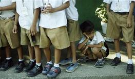 <p>A student sits in line for gifts and food during a Christmas outreach program for public school children at the Department of Education in Manila December 19, 2007. REUTERS/Cheryl Ravelo</p>