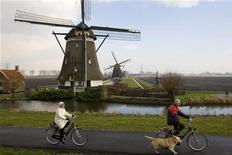 <p>Жители Голландии едут на велосипедах мимо ветряных мельниц. 7 февраля 2007 года. Вне зависимости от экономической обстановки влюбленные в велосипеды голландцы продолжают тратить на них колоссальные суммы - около миллиарда евро в год. REUTERS/Michael Kooren</p>