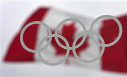 <p>The Olympic rings are framed by the Canadian flag in downtown Vancouver, British Columbia January 14, 2010. REUTERS/Andy Clark</p>