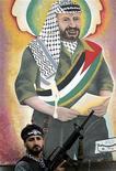 <p>Вооруженный палестинец стоит перед изображением скончавшегося палестинского лидера Ясира Арафата недалеко от города Наблус 10 января 2005 года. В 1969 году Ясир Арафат был избран новым лидером Организации освобождения Палестины. REUTERS/Abed Omar Qusini</p>