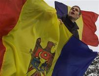 <p>Румынский студент поет и держит молдавский флаг во время протестов в Бухаресте 25 января 2004 года. Прозападные власти Молдавии вопреки протестам оппозиционных коммунистов приступили в среду к демонтажу колючей проволоки на границе с Румынией. REUTERS/Bogdan Cristel</p>