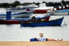 <p>A woman reads a book as she enjoys the warm weather at Las Teresitas beach on the island of Tenerife in Spain's Canary Islands January 12, 2010. REUTERS/Santiago Ferrero</p>