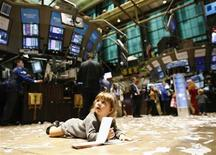 <p>A child lies on the trading floor during kid's day at the New York Stock Exchange, November 27, 2009. REUTERS/Brendan McDermid</p>