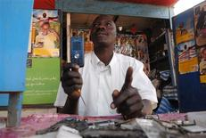 <p>Mohammed Abakar Mohammed mends a Chinese mobile phone at his stall in Abu Shouk Camp in Darfur February 11, 2010. REUTERS/Andrew Heavens</p>