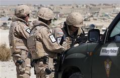 """<p>Офицеры хорватской военной полиции изучают карту во время патруля в Кабуле 16 октября 2009 года. По меньшей мере 14 человек погибли и еще 32 получили ранения в результате атаки боевиков движения """"Талибан"""" в афганской столице, сообщили местные власти. REUTERS/Nikola Solic</p>"""