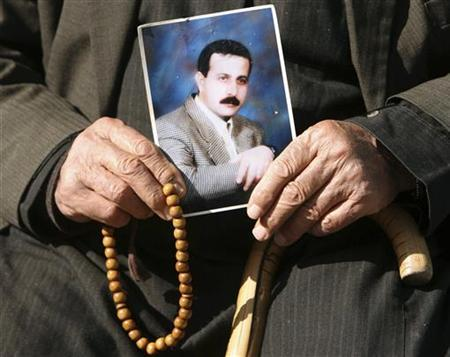The father of senior Hamas military commander Mahmoud al-Mabhouh poses with a picture of his son outside his family's house in Jabalya in the northern Gaza Strip February 22, 2010. REUTERS/Mohammed Salem