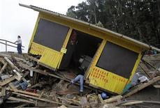 <p>Чилиец пытается достать свои вещи из разрушенного в результате землетрясения здания, 28 февраля 2010 года. Число жертв землетрясений в Чили удвоилось за воскресенье и превысило 700 человек после новых подземных толчков и цунами на побережье. REUTERS/Ivan Alvarado</p>