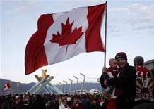 <p>A Canadian holding a child and a national flag stands in front of the Olympic cauldron during celebrations for Canada's victory over the U.S. in the men's ice hockey gold medal game at the Vancouver 2010 Winter Olympics, February 28, 2010. REUTERS/Chris Helgren</p>