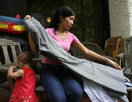 Susan, a 36-year-old maid from the Philippines, works at her employer's house in Singapore April 29, 2008. REUTERS/Vivek Prakash