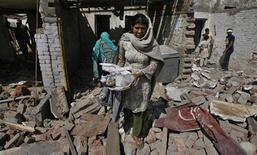 <p>Женщина выносит из дома, разрушенного в результате взрыва бомб, сохранившиеся вещи, Лахор, Пакистан, 9 марта 2010 года. Не менее 20 человек погибли и более 50 получили ранения при взрывах, осуществленных боевиками-смертниками в пакистанском городе Лахор, сообщили местные власти. REUTERS/Mohsin Raza</p>