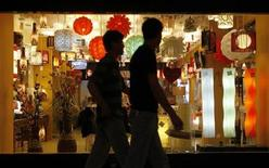 <p>Customers walk past a shop selling lights in a shopping mall located in central Beijing August 11, 2009. REUTERS/David Gray</p>