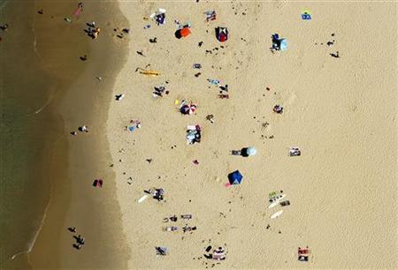 People sunbathe on Nobbys Beach on a hot autumn day in the city of Newcastle, March 11, 2007. REUTERS/David Gray