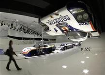 <p>A visitor passes a Porsche 956 (R) hanging on the ceiling in the newly built Porsche Museum in Stuttgart January 26, 2009. REUTERS/Michaela Rehle</p>