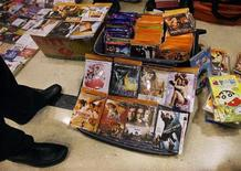<p>A customer looks at pirated DVDs at an alley in Beijing December 13, 2007. REUTERS/Claro Cortes IV</p>