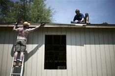<p>Volunteers work at the roof of a rebuilt house destroyed by hurricane Katrina at Pearlington, Mississippi, May 10, 2007. REUTERS/Carlos Barria</p>