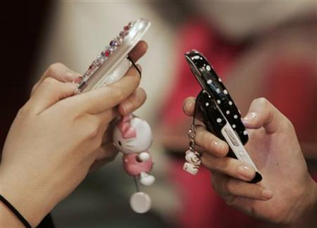 Middle-school girls use mobile phones as they chat in a restaurant in Seoul December 15, 2006. REUTERS/Kim Kyung-Hoon